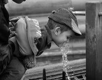 喝少许水的男孩 免版税图库摄影