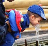 喝少许水的男孩 库存图片