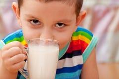 喝少许牛奶纵向的男孩特写镜头 免版税库存照片
