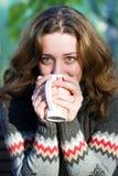 喝户外俏丽的妇女的咖啡 免版税库存图片