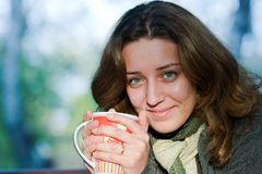 喝户外俏丽的茶妇女 免版税库存照片