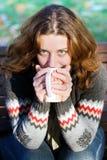 喝户外俏丽的茶妇女 图库摄影