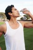 喝拉丁美州的男性水年轻人的运动员 图库摄影
