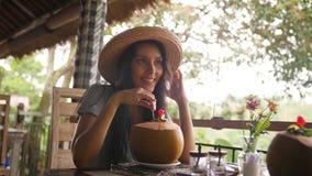 喝新鲜的年轻椰子水鸡尾酒的可爱的年轻旅游行家女孩在有美丽的热带密林的餐馆 股票录像