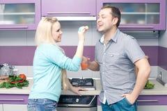 喝新鲜的柑橘汁的逗人喜爱的年轻夫妇画象  库存照片