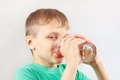 喝新鲜的柠檬水的小滑稽的男孩 图库摄影