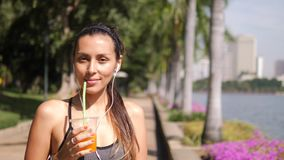 喝新鲜的橙汁的可爱的混合的族种瑜伽女孩在锻炼以后在城市公园 4k,慢动作 泰国 影视素材