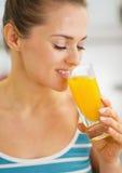 喝新鲜的橙汁的愉快的妇女 免版税库存照片