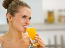 喝新鲜的橙汁的愉快的少妇 免版税库存图片