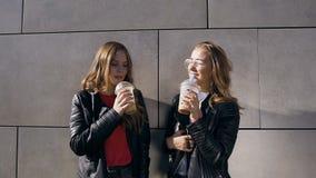 喝新鲜的汁液的两个女孩画象,当站立在街道在现代大厦附近灰色墙壁在晴朗时的温暖 影视素材