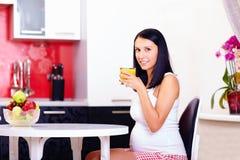 喝新鲜的汁液的孕妇在厨房里 免版税库存照片