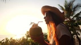 喝新鲜的泰国椰子水Coctail的可爱的年轻混合的族种旅游女孩在海滩反对美好的日落 4K 股票视频