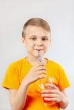 喝新鲜的红色柠檬水的小滑稽的男孩通过秸杆 免版税库存图片