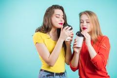 喝早晨咖啡的两个微笑的学生女孩,吸入咖啡芳香  乐趣,放松,幸福 库存照片