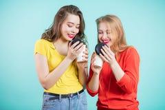 喝早晨咖啡的两个微笑的学生女孩,吸入咖啡芳香  免版税库存照片