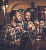 喝桶装啤酒的最佳的riends在酒吧柜台在客栈 免版税图库摄影