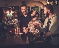 喝桶装啤酒的老朋友在酒吧柜台在客栈 免版税库存照片