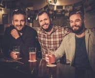 喝桶装啤酒的老朋友在酒吧柜台在客栈 免版税库存图片