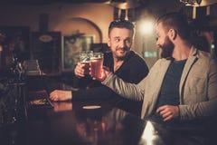 喝桶装啤酒的老朋友在酒吧柜台在客栈 库存照片