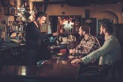 喝桶装啤酒的老朋友在酒吧柜台在客栈 图库摄影