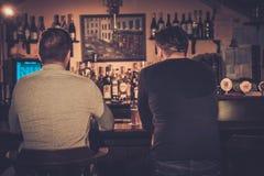 喝桶装啤酒的老朋友在酒吧柜台在客栈 库存图片