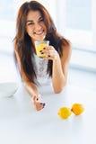 喝橙汁和微笑对t的健康早餐妇女 库存图片