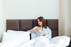 喝橙汁的一名深色的妇女的画象,当在家时坐床 免版税库存图片