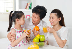 喝橙汁的亚洲家庭。 库存照片