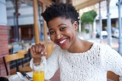 喝橙汁的可爱的年轻黑人妇女在餐馆 图库摄影