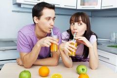 喝橙汁的夫妇在厨房里 免版税库存图片