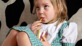 喝橙汁的孩子坐长沙发,看电视,孩子的小女孩 影视素材