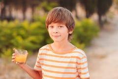 喝橙汁的孩子男孩 库存照片