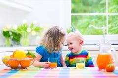 喝橙汁的孩子 免版税库存照片