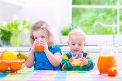 喝橙汁的孩子 免版税库存图片