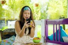 喝橙汁的年轻美丽和愉快的亚裔中国妇女画象使用互联网手机在有机食品咖啡 免版税库存照片