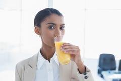 喝橙汁的微笑的典雅的女实业家 免版税库存照片