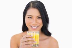 喝橙汁的微笑的肉欲的裸体模特儿 免版税库存照片