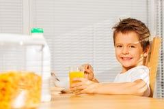 喝橙汁的愉快的男孩在早餐 免版税库存照片
