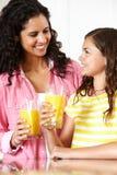 喝橙汁的母亲和女儿 免版税库存图片