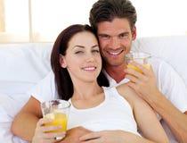 喝橙汁的浪漫夫妇 库存照片