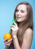 喝橙汁的美丽的女孩通过秸杆 免版税库存照片