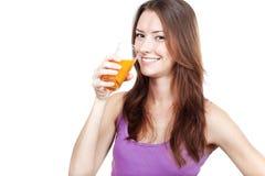 喝橙汁的美丽的深色的妇女 免版税库存图片