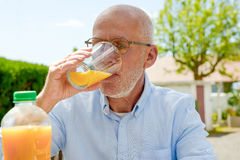 喝橙汁的老人在她的庭院里 免版税库存图片