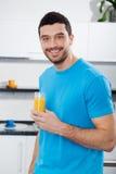 喝橙汁的英俊的人 免版税库存照片