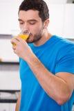 喝橙汁的英俊的人 免版税图库摄影