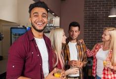 喝橙汁谈的笑的坐的人朋友在酒吧柜台,混合种族人愉快微笑 库存图片