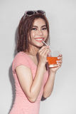 喝橙汁posin的性感的亚裔可爱的深色的妇女 免版税库存照片