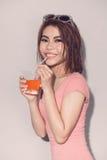 喝橙汁posin的性感的亚裔可爱的深色的妇女 免版税库存图片