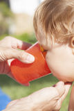 喝橙色杯子的婴孩 库存图片