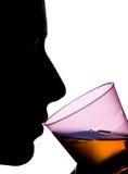 喝橙色液体的妇女的被隔绝的剪影 免版税库存照片